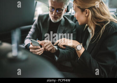 Young woman with senior businessman using mobile phone while traveling by a car. Business people using smart phone in taxi. - Stock Photo