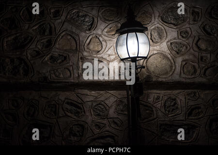 Old lamp lighting a spot on a stone wall - Stock Photo
