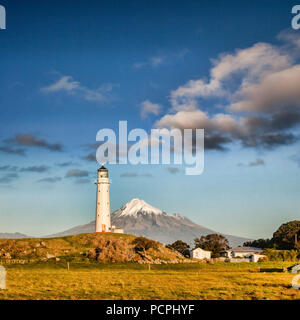Mount Taranaki, also known as Mount Egmont, and Cape Egmont Lighthouse, Taranaki, New Zealand, at sunset. - Stock Photo