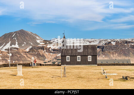 16 April 2018: Budir, Snaefellsnes Peninsula, West Iceland - The Little Black Church, and a family of tourists visiting. - Stock Photo