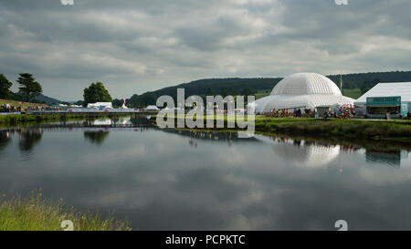 RHS Chatsworth Flower Show showground (people visiting, marquee, tents, Great Conservatory dome & bridge reflected in river) Derbyshire, England, UK. - Stock Photo