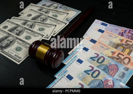 Judge's gavel on the background of euro and dollar bills on wooden background - Stock Photo