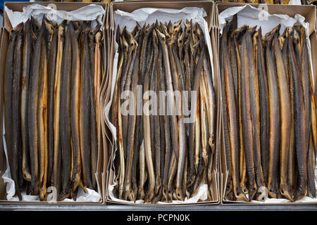 Fresh smoked eels in cardboard boxes for sale - Stock Photo