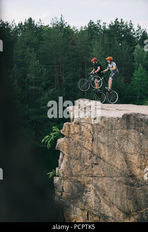 side view of trial bikers standing on back wheels on rocky cliff with blurred pine forest on background - Stock Photo