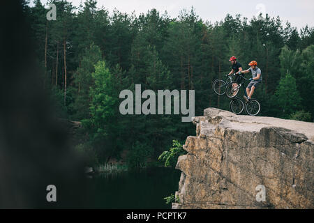side view of extreme trial bikers standing on back wheels on rocky cliff with blurred pine forest on background - Stock Photo