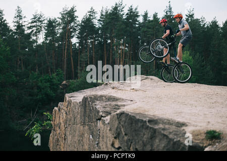 active young trial bikers standing on back wheels on rocky cliff with blurred pine forest on background - Stock Photo