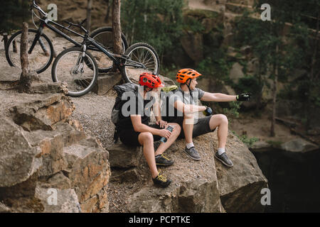 high angle view of young trial bikers relaxing on rocky cliff after ride and looking away - Stock Photo