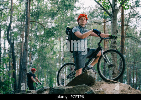 young trial biker standing on rock at beautiful forest and looking away with his friend blurred on background - Stock Photo