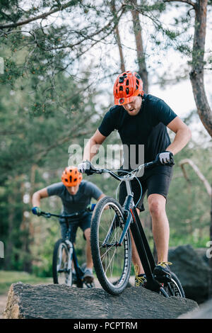 young trial bikers performing stunts on boulders - Stock Photo