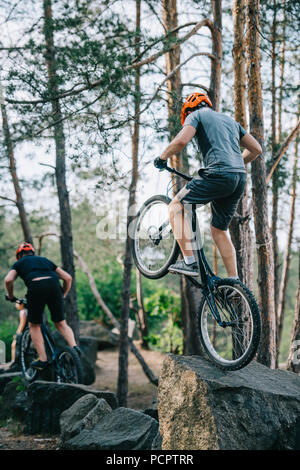 athletic young trial bikers performing stunts on boulders - Stock Photo