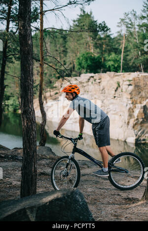 young trial biker riding outdoors in front of lake at forest - Stock Photo