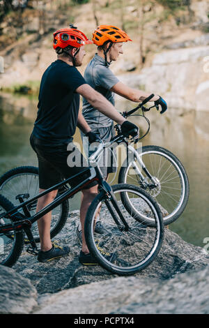 young trial bikers standing on rocky cliff in front of mountain lake and looking away - Stock Photo