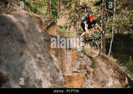 young trial biker riding downhill outdoors in pine forest - Stock Photo