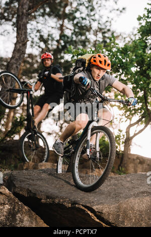 young trial bikers riding on rocks at pine forest - Stock Photo