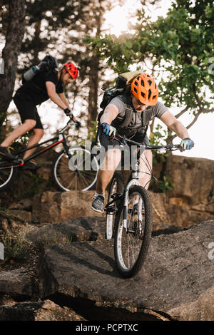 extreme young trial bikers riding on rocks at pine forest - Stock Photo