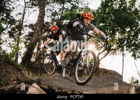athletic young trial bikers riding on rocks at pine forest - Stock Photo