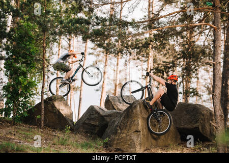 active trial bikers performing stunts on rocks outdoors - Stock Photo