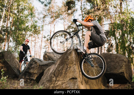 extreme trial bikers riding on rocks outdoors - Stock Photo