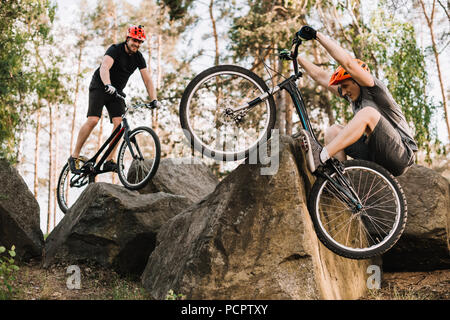 active young trial bikers riding on rocks outdoors - Stock Photo
