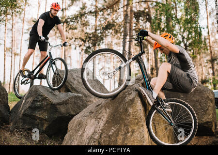 athletic young trial bikers riding on rocks outdoors - Stock Photo