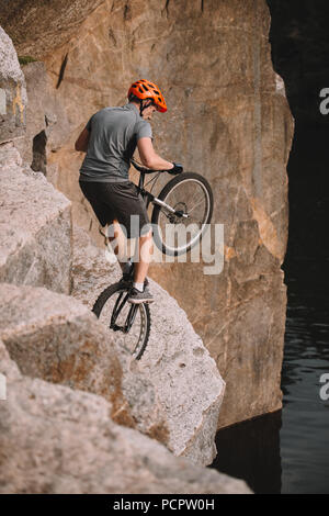 high angle view of trial biker balancing on back wheel on rocks outdoors - Stock Photo