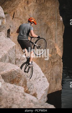 high angle view of trial biker balancing on back wheel on rocks outdoors
