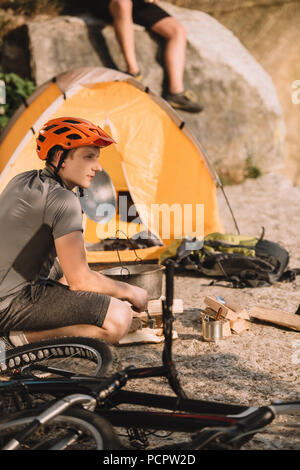 athletic young bike traveller sitting on rocks with camping tent and blurred friend sitting on background - Stock Photo