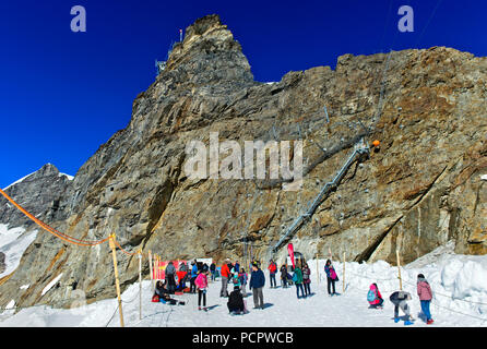 At a hot summer day, tourists enjoy snow at 3466 meter above sea level on the Jungfraujoch, Grindelwald, Bernese Alps, Switzerland - Stock Photo
