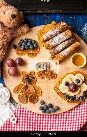 Children's breakfast. Pancakes with berries and warriors, with cheerful faces. Top view. - Stock Photo