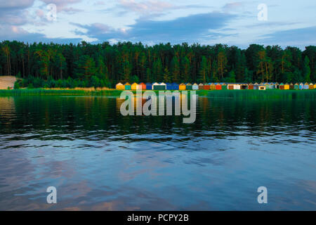 Colorful boat house on the edge of the water. Bright orange, red, green building is a waterside garage for boats. Concepts of buildings, structures, l - Stock Photo