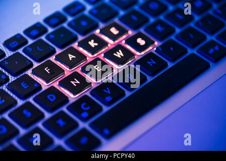 Fake news written in red on a backlit laptop keyboard close-up with selective focus in a blue ambiant light - Stock Photo