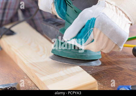 Man sanding a wood with orbital sander in a workshop - Stock Photo