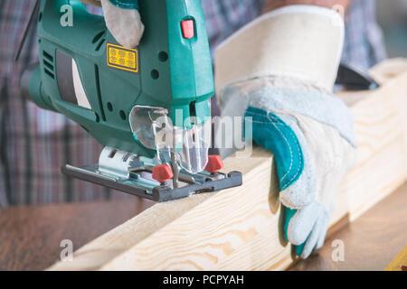 Man cutting a piece of wood using a jigsaw - Stock Photo
