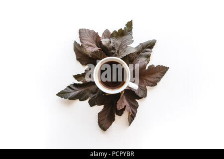 A cup of aromatic espresso or black tea. Nearby lie autumn leaves. Simple minimalistic autumn design. - Stock Photo