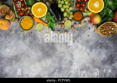 Healthy food background, frame of organic food. Ingredients for healthy cooking: vegetables, fruits, nuts, spices. Balanced diet food on a dark black - Stock Photo