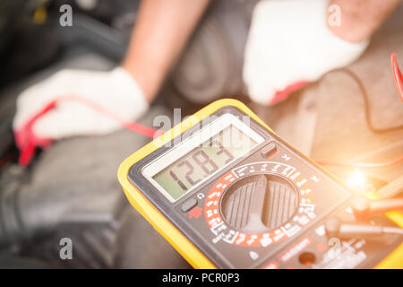 Car mechanic uses a multimeter to check car battery voltage - Stock Photo