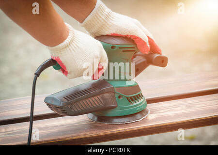 Sanding a wood with orbital sander outdoor - Stock Photo