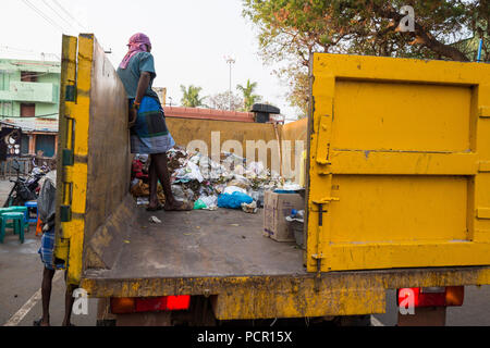 Indian woman take garbage in the street - Stock Photo