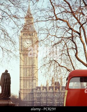 Palace of Westminster, London, c1945-c1980. The clock tower of the Houses of Parliament viewed from Parliament Square. The huge bell housed in the clock tower and known as Big Ben came into operation in 1859. A red London bus is passing. - Stock Photo