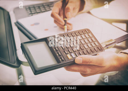 Womans hand holding calculator and writing with pen, financial chart report and notebook on desk at office. - Stock Photo
