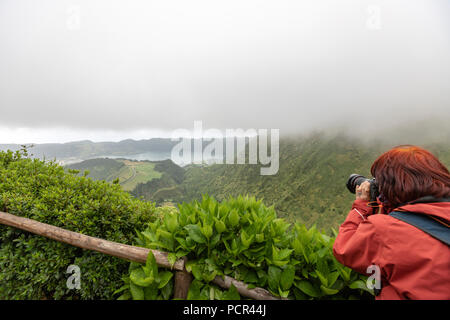 Tourist on Lagoa do Canario Miradouro, viewpoint, in a foggy and rainy day and Santiago Lake and part of Sete Cidades Lake. Sao Miguel island, Azores - Stock Photo