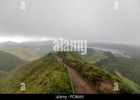 Tourist on a path leading to Lagoa do Canario Miradouro, viewpoint, and Santiago Lake and part of Sete Cidades Lake. Sao Miguel island, Azores. - Stock Photo