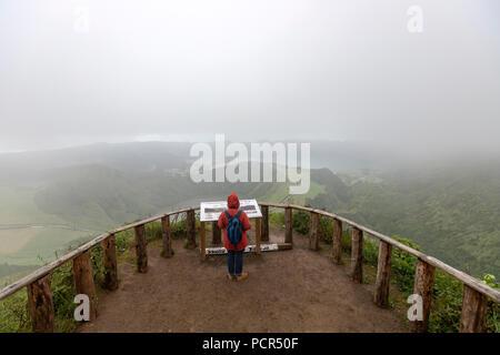 Tourist on Lagoa do Canario Miradouro, viewpoint, in a foggy and rainy day and Santiago Lake and part of Sete Cidades Lake. Sao Miguel island, Azores - Stock Photo