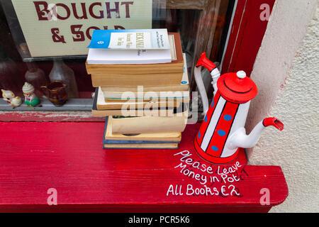 second hand softback books for sale on a window ledge. - Stock Photo