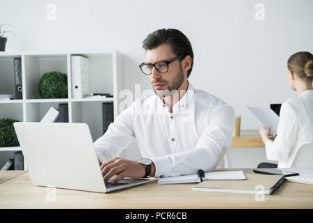 focused young businessman working with laptop at modern office with colleague sitting on background - Stock Photo