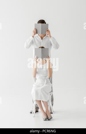 woman in linen white dress sitting on chair and covering face by book while her boyfriend standing behind and covering face by book isolated on grey b - Stock Photo