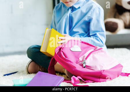 cropped shot of smiling child holding book while packing school bag - Stock Photo
