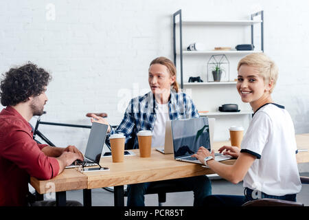 smiling young business colleagues working with digital devices - Stock Photo