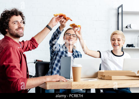 happy young business colleagues eating pizza and smiling at camera - Stock Photo