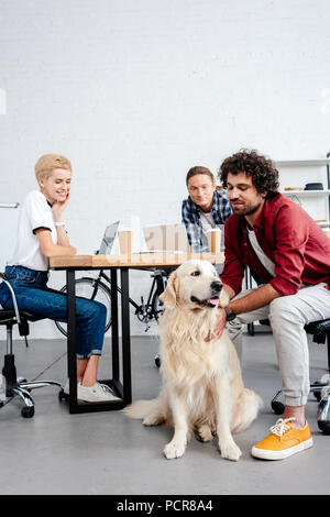 smiling young business colleagues looking at dog while working in office - Stock Photo